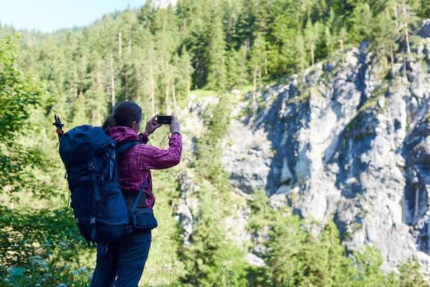 Grimpeur femelle faisant photo de spectaculaire rocher vert avec de hauts arbres sur le dessus