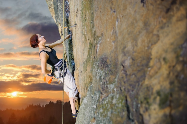 Grimpeur femme escalade avec une corde sur un mur rocheux