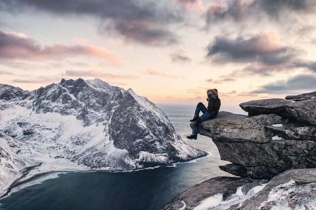 Grimpeur homme assis sur la crête rocheuse avec vue sur la montagne enneigée sur le mont ryten en soirée