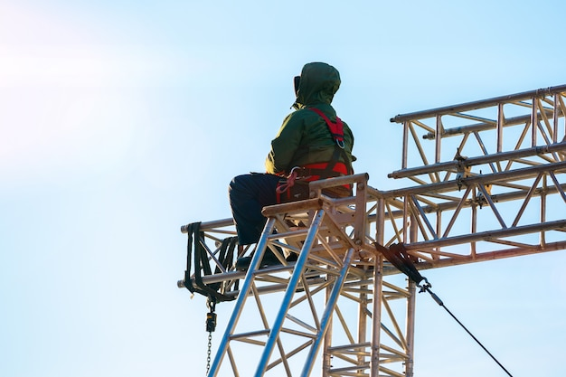 Grimpeur industriel en uniforme assis ts sur une structure de bâtiment