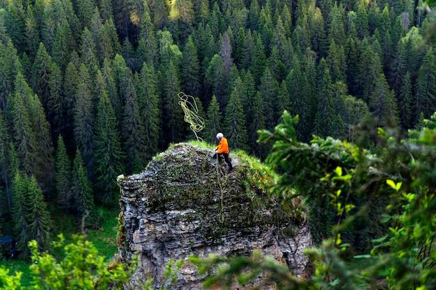 Grimpeur lance une corde se préparant à descendre du haut d'une falaise abrupte