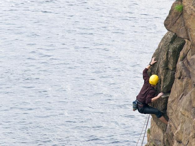 Un grimpeur masculin actif s'élevant sur la roche de mer