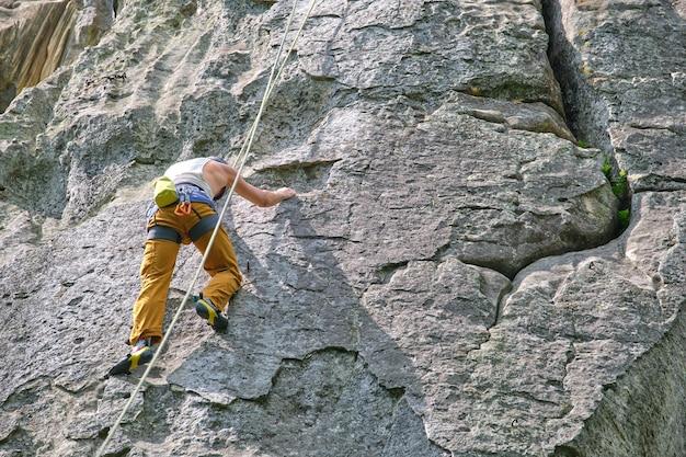 Grimpeur masculin fort escaladant le mur escarpé de la montagne rocheuse. sportif surmontant la route difficile. s'engager dans le concept de passe-temps de sports extrêmes.