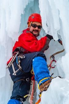 Grimpeur masculin souriant avec piolet parmi les glaçons d'une cascade gelée