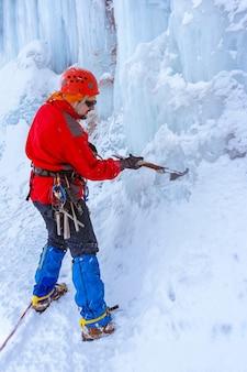 Un grimpeur avec un piolet coupe la glace, fait des pas dans le glacier