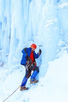 Grimpeur avec piolet se prépare à escalader un mur de glace enneigé