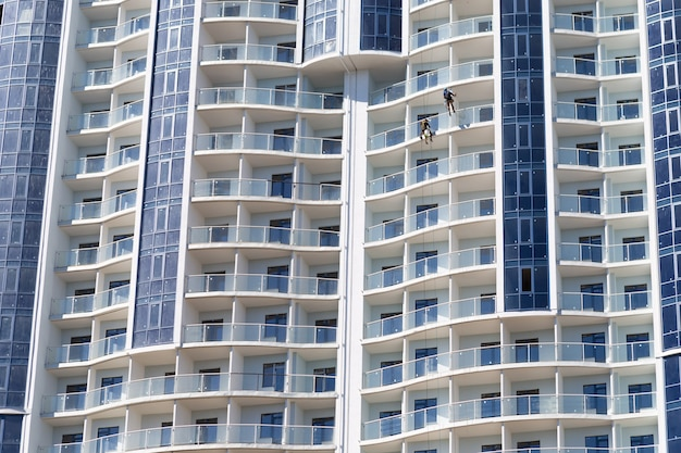 Grimpeurs industriels travaillant sur la construction de gratte-ciel sur ciel bleu, architecture moderne, bâtiment urbain.
