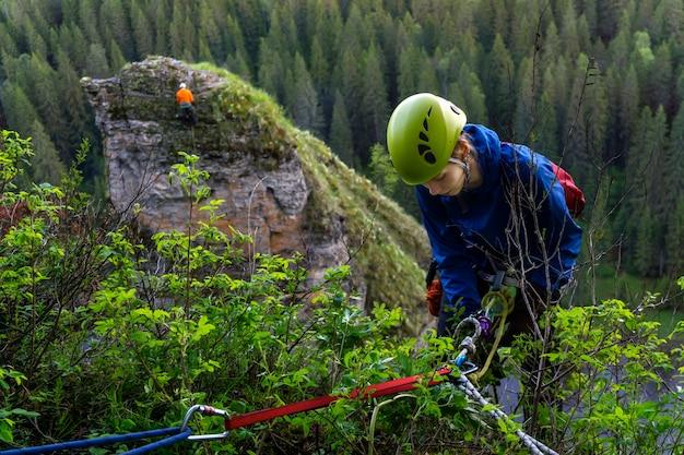Une grimpeuse commence la descente de la falaise avec une corde et un équipement de sécurité