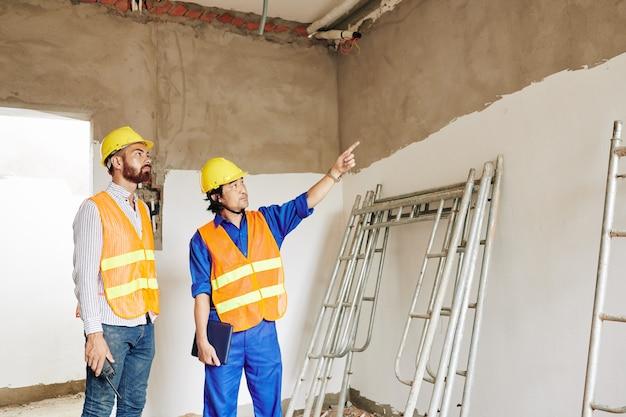Grincheux constructeur montrant un toit qui fuit dans la salle du bâtiment en construction à l'entrepreneur