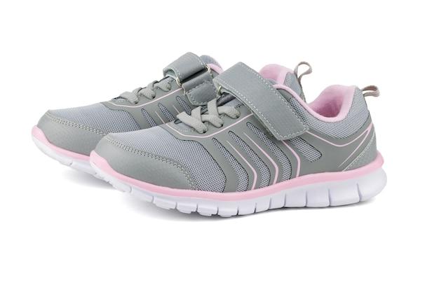 Gris avec des baskets pour enfants roses isolés sur une surface blanche. chaussures de sport modernes.