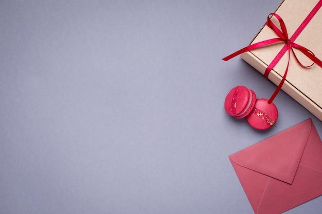 Gris avec enveloppes-cadeaux, boîte-cadeau et macarons