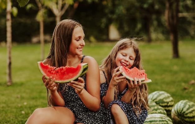 Grls aux cheveux longs en robes d'été assis sur un tas de pastèques et en mangeant des tranches.