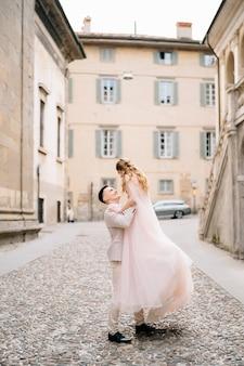 Groom cercles mariée dans ses bras debout sur les pavés près de l'ancien bâtiment à bergame italie