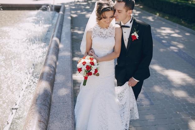Groom embrasser la mariée près de la fontaine