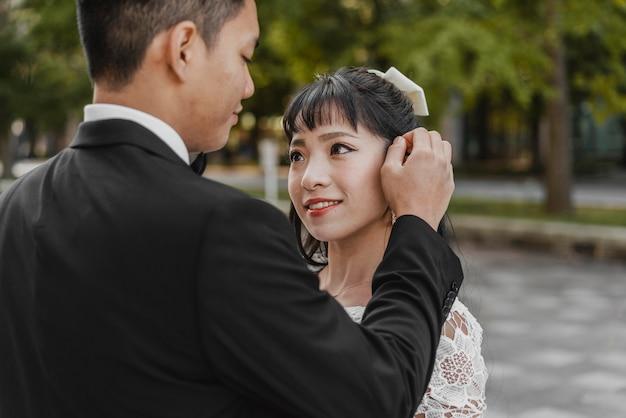 Groom fixant les cheveux de la mariée à l'extérieur