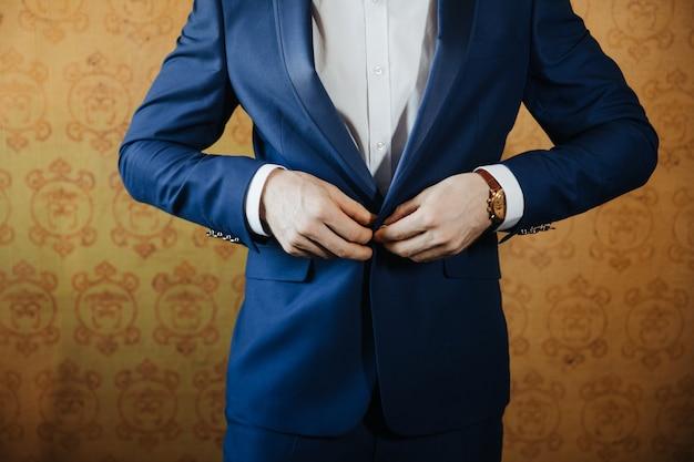 Groom habille le bouton de costume