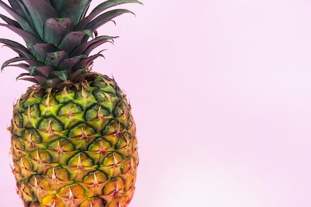 Un gros ananas sur fond rose isolé. style minimaliste.