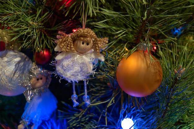 Gros anges et boule sur l'arbre de noël. détail de l'arbre de noël décoré de beaux ornements. vacances de noël nature morte.