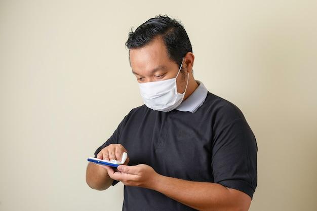 Un gros asiatique portant un masque nettoie son smartphone à l'aide de lingettes nettoyantes, pour empêcher la propagation du virus corona