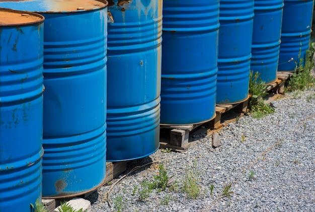 Gros bidons d'huile, bleus. barils chimiques dans un entrepôt ouvert.