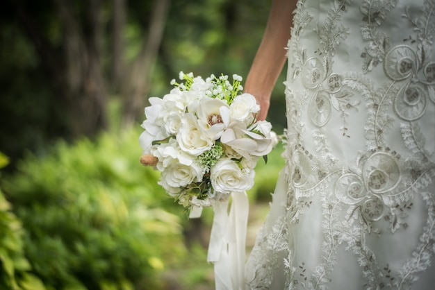 Gros bouquet de mariée dans la main de la mariée.
