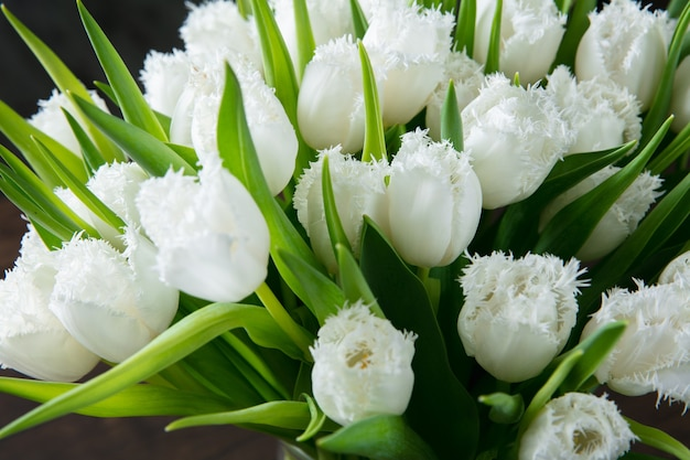 Gros bouquet de mode moderne de différentes fleurs sur fond en bois. cadeau pour la mariée le mariage, la fête des mères, la fête de la femme. mode printanière romantique. tulipes tendres et d'un blanc pur.