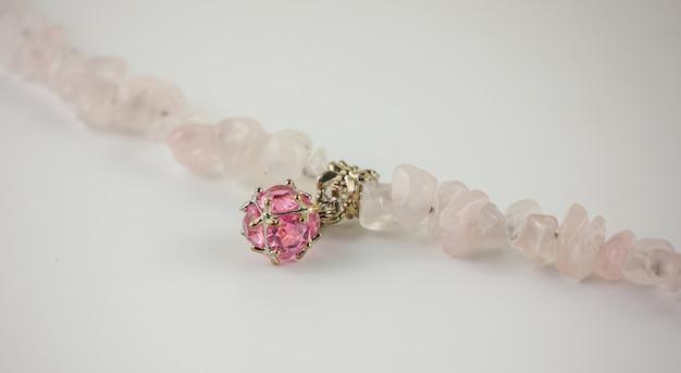 Gros bracelet en quartz rose et cristal sur fond blanc