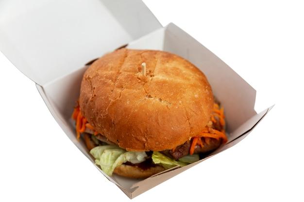 Gros burger alléchant dans une boîte en carton. la malbouffe et la restauration rapide. isolé sur fond blanc.