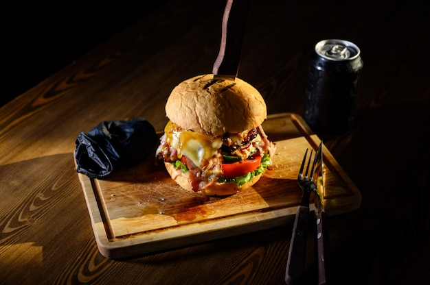Gros burger juteux sur une planche à découper