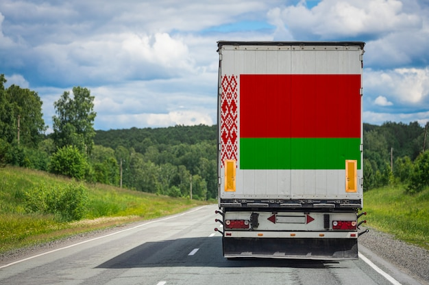 Gros camion avec le drapeau national du bélarus se déplaçant sur l'autoroute
