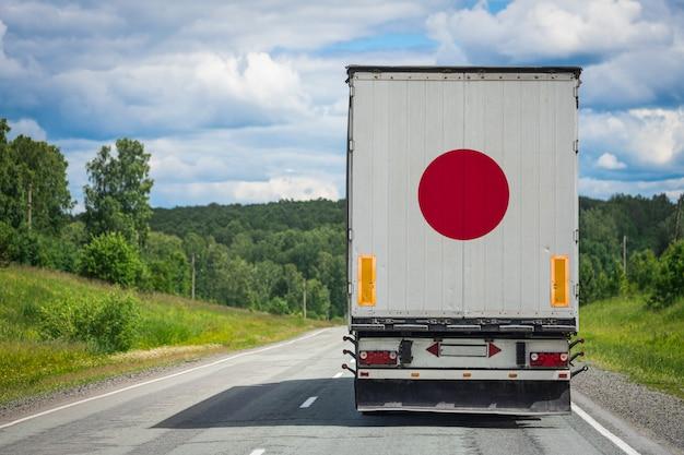 Gros camion avec le drapeau national du japon se déplaçant sur l'autoroute
