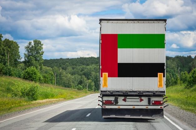 Gros camion avec le drapeau national des émirats arabes unis émet se déplaçant sur l'autoroute