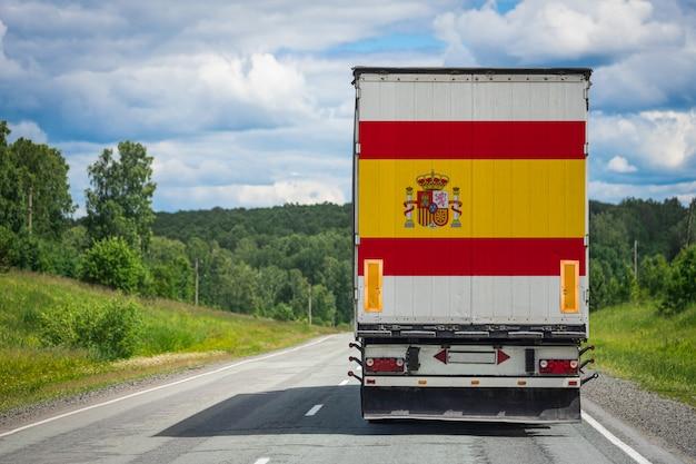 Gros camion avec le drapeau national de l'espagne se déplaçant sur l'autoroute