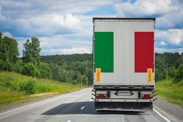 Gros camion avec le drapeau national de l'italie se déplaçant sur l'autoroute