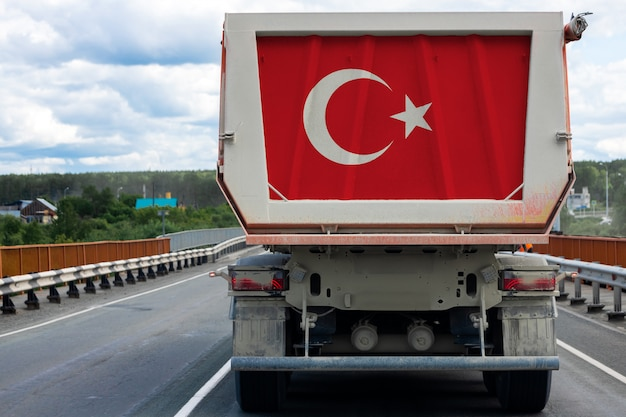 Gros camion avec le drapeau national de la turquie se déplaçant sur l'autoroute,