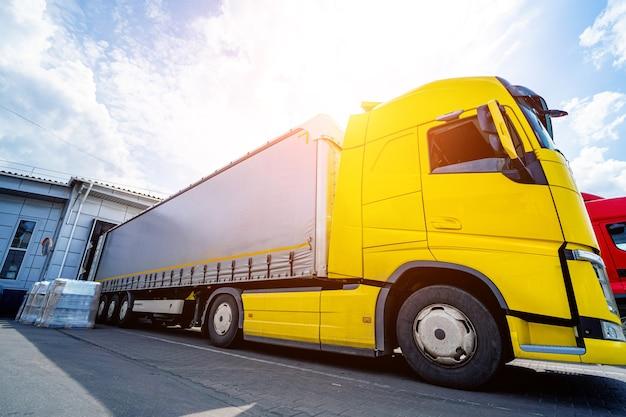 Gros camions près de l'entrepôt sur fond de ciel bleu