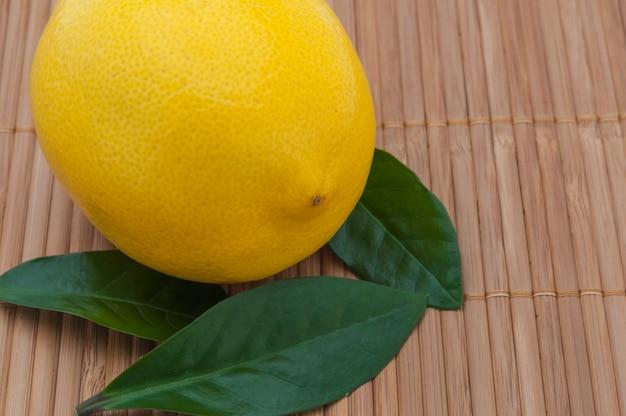 Gros citron jaune avec feuilles vertes gros plan sur la natte de bambou.