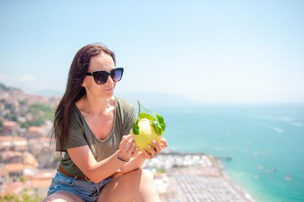 Gros citron jaune à la main en arrière-plan de la mer méditerranée et du ciel.