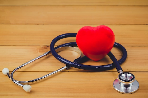 Gros coeur rouge et steythoscope sur une vieille table en bois