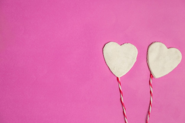 Gros coeurs sur fond rose avec un espace pour le texte, icône de l'amour, saint valentin