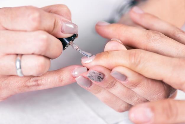 Gros coup d'une esthéticienne appliquant du vernis à ongles à un ongle féminin au salon de manucure.
