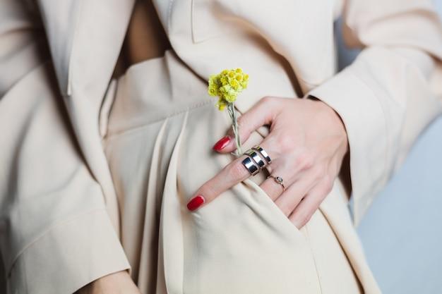 Gros coup de femme mains manucure rouge deux anneaux portant un costume beige. jolie fleur séchée jaune dans la poche.