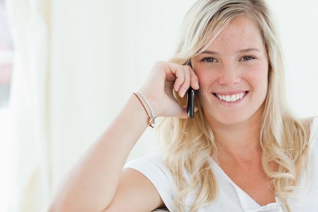 Gros coup d'une femme souriante alors qu'elle parle sur son téléphone
