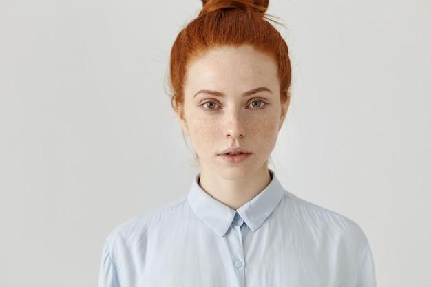 Gros coup de jolie jeune femme aux cheveux roux réussie en chemise formelle ayant un regard sérieux et confiant avant la journée de travail, posant au mur de bureau blanc. concept de personnes et de style de vie