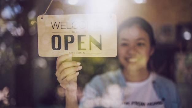 Gros coup de main de femme tournant panneau ouvert sur la porte en verre dans un café.