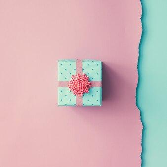 Gros coup de petit cadeau emballé avec un ruban rose sur un mur bleu rose. concept minimal. mise à plat. vue de dessus.