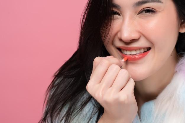 Gros coup recadrée de magnifique charmante femme asiatique tenant les lèvres.