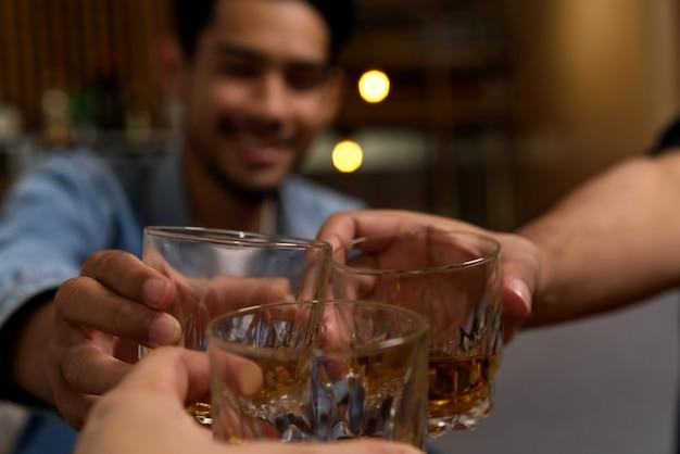 Gros coup de verres cliquetants entre groupe d'amis buvant du whisky à la fête au restaurant.