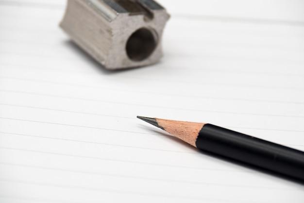Gros crayon, taille-crayon et cahier vierge sur fond en bois.