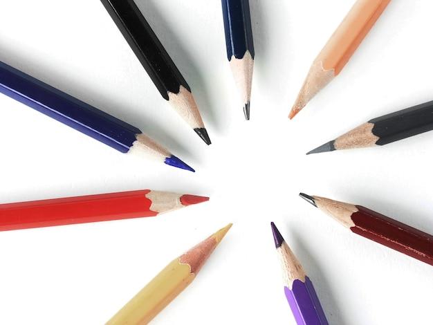 Gros crayons de couleur empilés en cercle sur fond blanc.